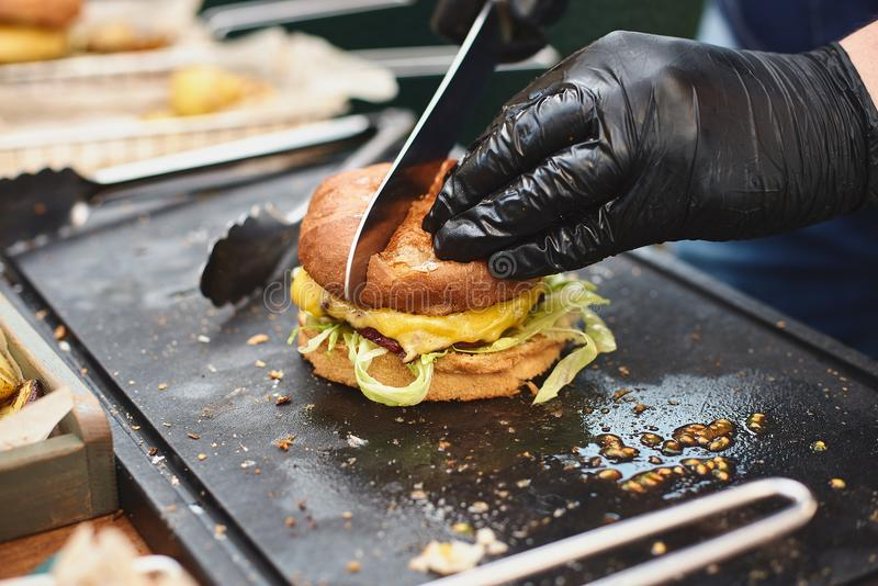 Close up of appetising beef burger. Chef`s hands divide into half cooked hamburgers from beef. Street food ready to stock photos
