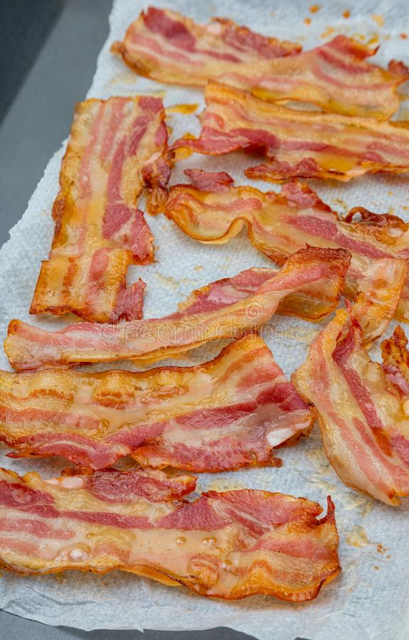 Close-up of appetizing slices of smoked bacon. Isolated on white background. With baking paper. Cooked in the oven, very crispy royalty free stock photos
