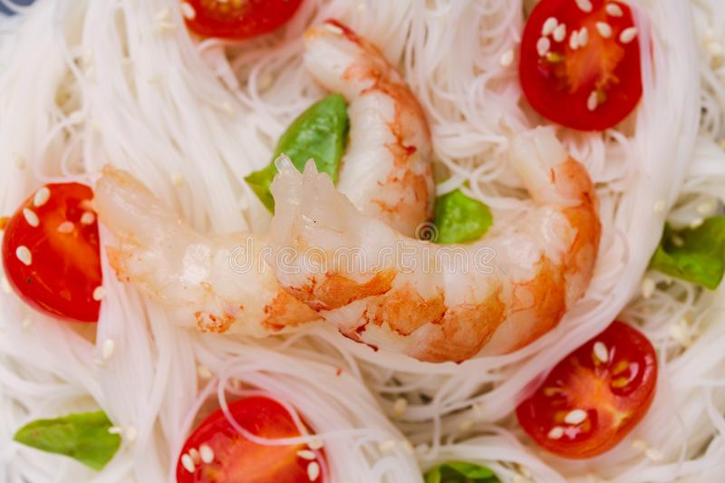 A close-up appetizing traditional pasta with noodles ,cherry, royal prawns and greens. Close-up. stock images