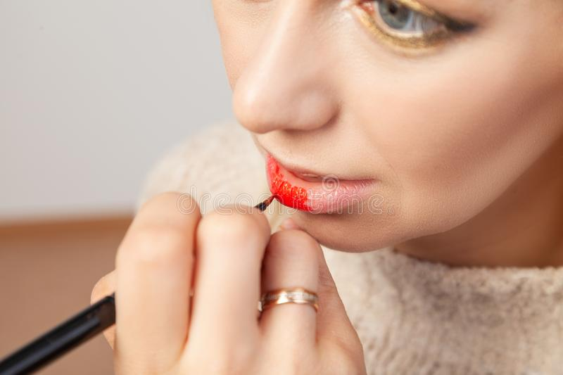 Close-up applying on the lips, the make-up artist holds a brush in her hand and applies red lipstick on the model`s open mouth stock photos