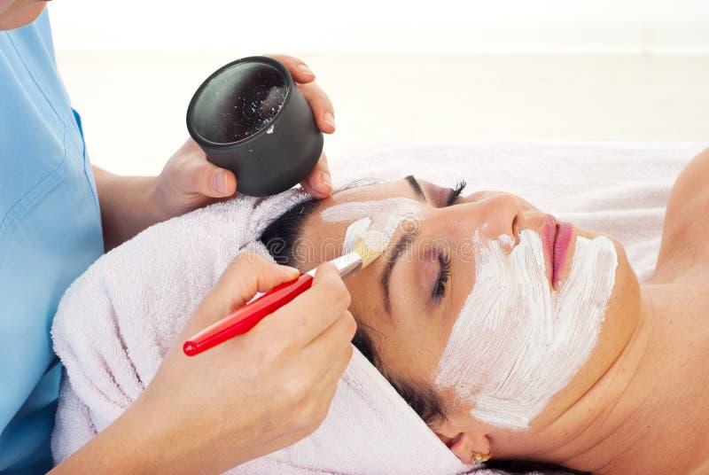 Close up of applying woman's facial mask royalty free stock photo