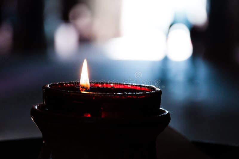 Close-up ardente de vidro vermelho da vela no interior escuro com luz no fundo fotografia de stock royalty free