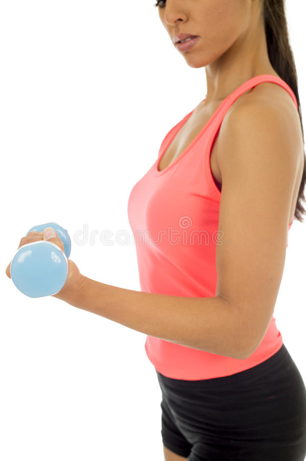 Close up arm and hand of young attractive happy latin woman in sport clothes holding weight dumbbell stock photo