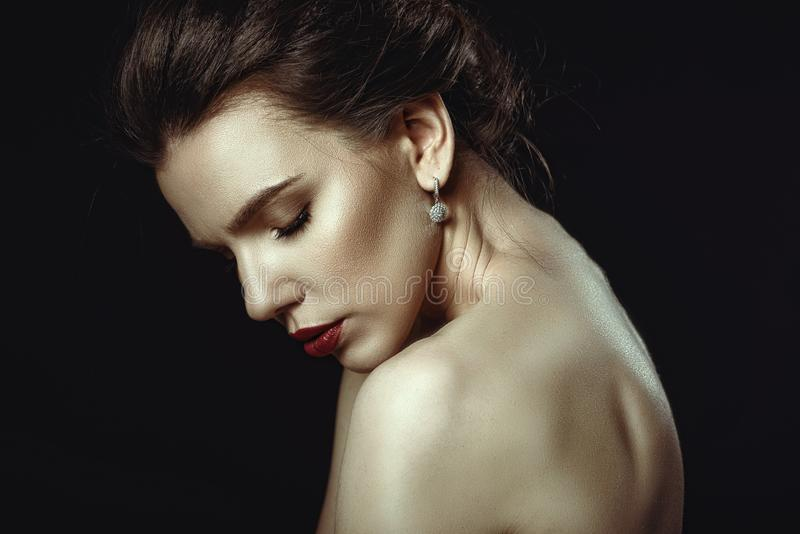 Close up art portrait of a woman with perfect make up and naked shoulders embracing herself with closed eyes royalty free stock photo