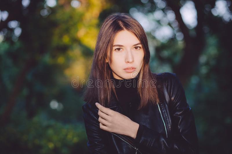Close up art portrait of a young pretty brunette woman posing outdoors in black leather coat in golden sunlight evening spot royalty free stock images
