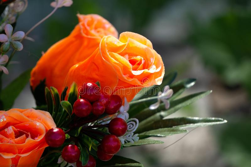 Close up of artificial orange coloured rose flower bouquet in soft focus background stock photos