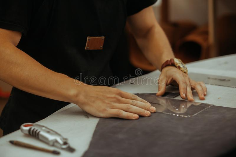 Close up of an artisan working with leather in his laboratory using tools. Handmade concept. Leather craft royalty free stock images