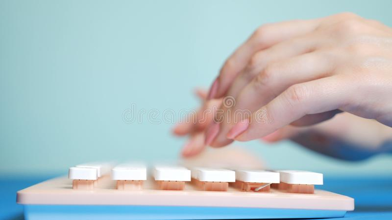 Close-up As m?os f?meas est?o datilografando em um teclado cor-de-rosa, em um fundo azul fotos de stock