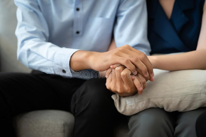 Close-up of Asian couple join hand give to encourage while sitting on the couch in the room to consult mental health problems by d. Octor. Health and illness royalty free stock photo