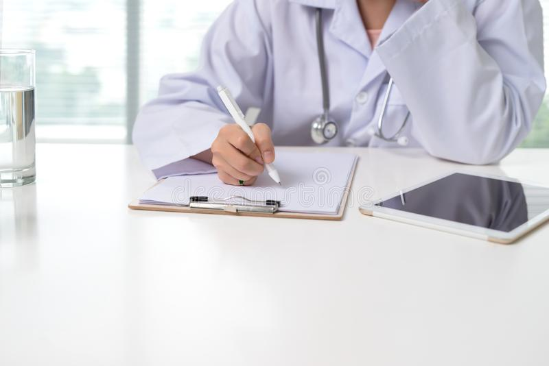 Close up on asian female doctor hands writing something on clipboard royalty free stock photos