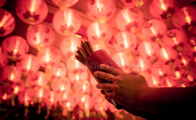 Close up of Asian hand holding fortune sticks or Seam-Si or Chi-Chi sticks, shake for future fore with red Chinese paper lamp. royalty free stock images