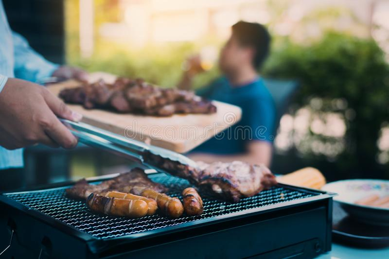 Close up asian hand man are pinching the pork on the grill and holding it to friends who are celebrating in the back stock photo