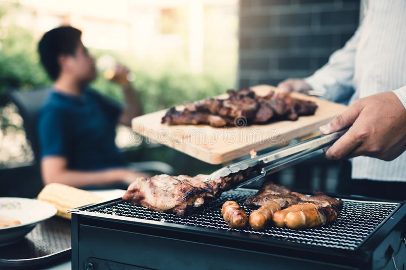 Close up asian hand man are pinching the pork on the grill and holding it to friends who are celebrating in the back stock image