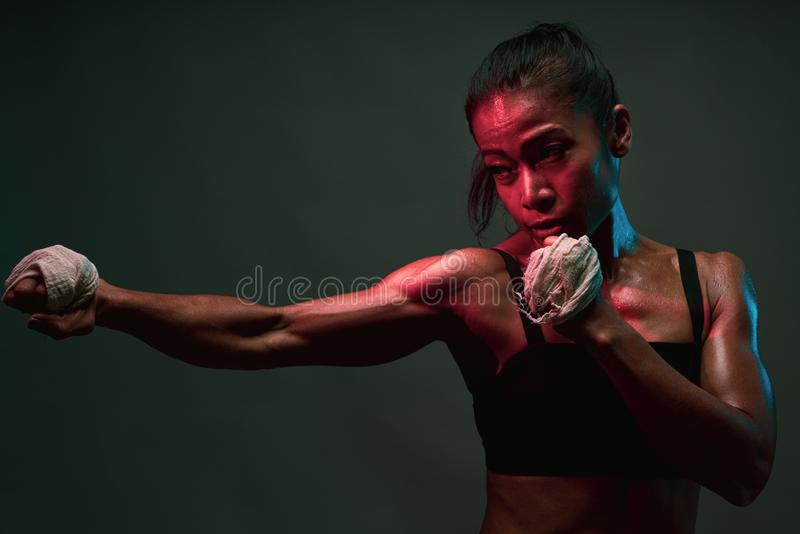 Close up of asian heathly woman shadow punching in boxing training with muscle fit lean tone body in pink and blue neon light on stock photos