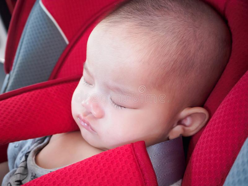 Asian infant baby girl sleep in the car seat with security belt. Close up asian infant baby girl sleep in the car seat with security belt for safety travel stock image