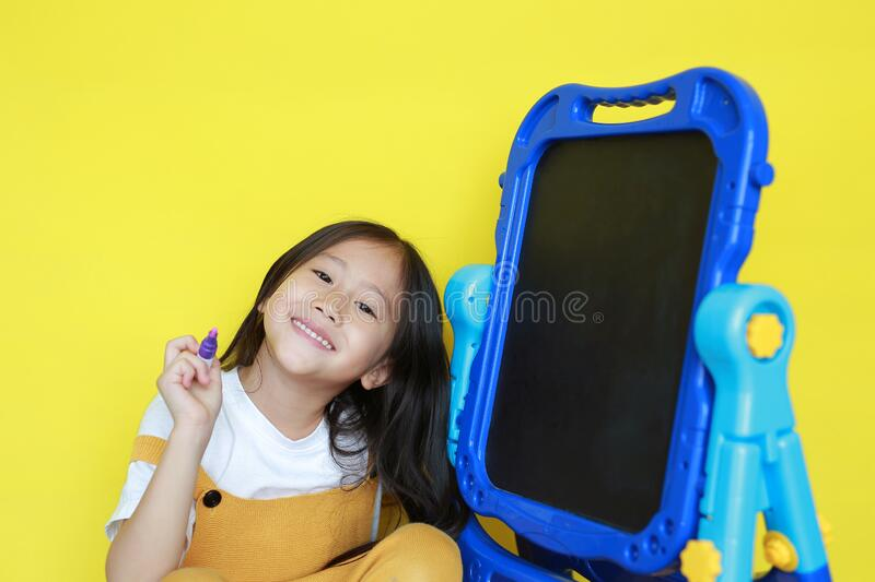 Close up asian little child girl with writing and drawing on empty blackboard over yellow background. Student and development royalty free stock photos