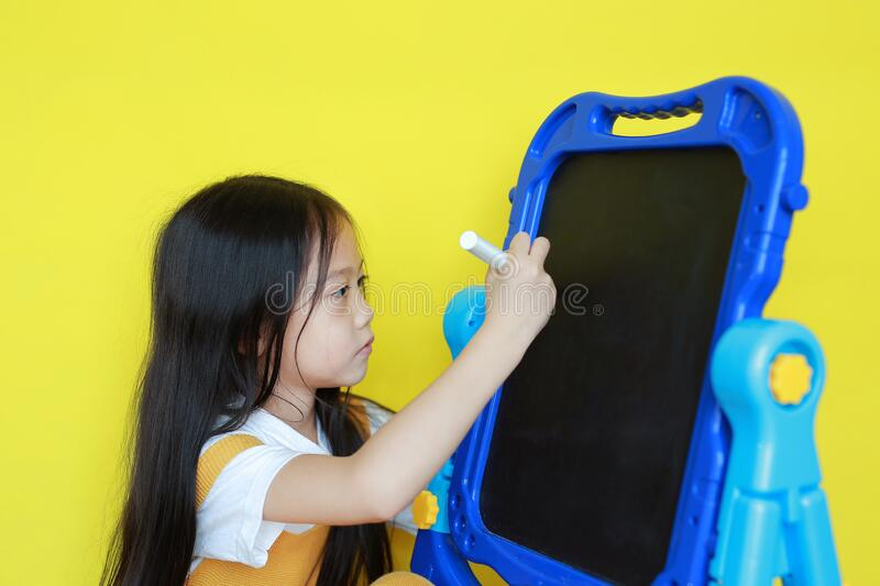 Close-up asian little girl writing on empty blackboard. Student and development concept royalty free stock photo