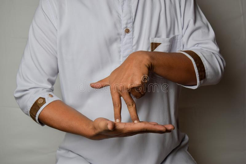 Close up Asian man shows hand gestures it means STAND isolated on white background. American sign language royalty free stock image