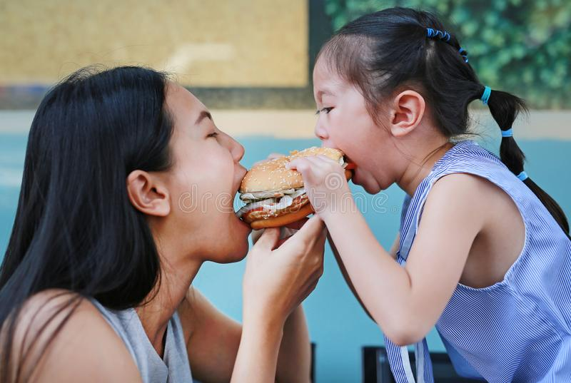 Close up Asian mother with child girl eating a hamburger together stock photography