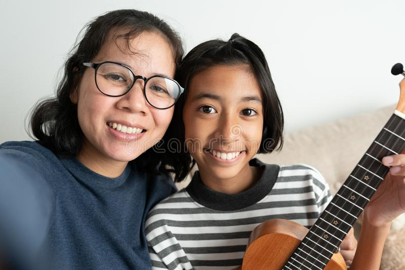 Close-up of an Asian mother and daughter taking a selfie and smiling while sitting on the sofa. The little girl holding a ukulele royalty free stock images