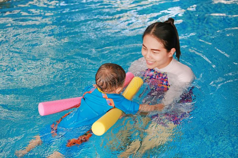 Close-up Asian mother teaching baby boy in swimming pool with noodle foam royalty free stock photo