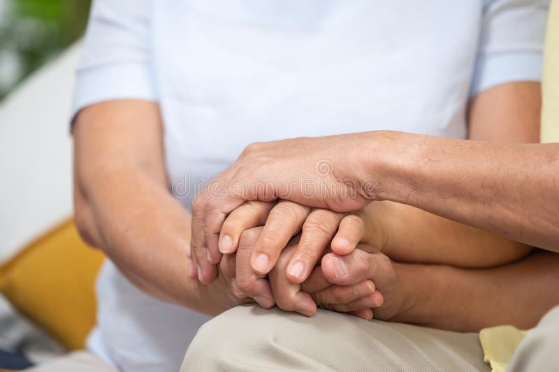 Close up Asian senior couple encouraging together by holding hand each other at sofa in living room at home.Happy retirement royalty free stock photos