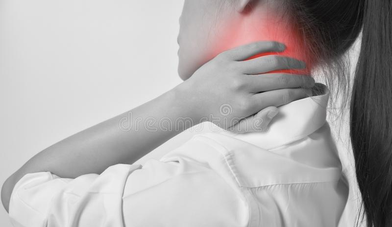 Close-up of Asian women acute pain in a neck, Health care and medical concept. gray background. stock photos