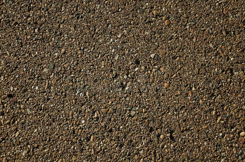 Close-up of asphalt with gravel inserted in it. Close-up of asphalt with small gravel inserted in it, on a countryside road at sunset near Elvas. A gracious star stock photos