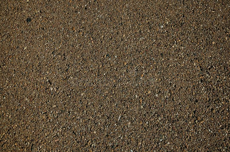 Close-up of asphalt with gravel inserted in it. Close-up of asphalt with small gravel inserted in it, on a countryside road at sunset near Elvas. A gracious star royalty free stock image