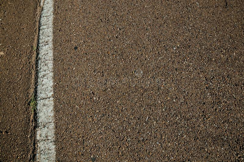 Close-up of asphalt and street lane on a road. Close-up of asphalt with small gravel inserted and a street lane, on a countryside road at sunset near Elvas. A royalty free stock photography