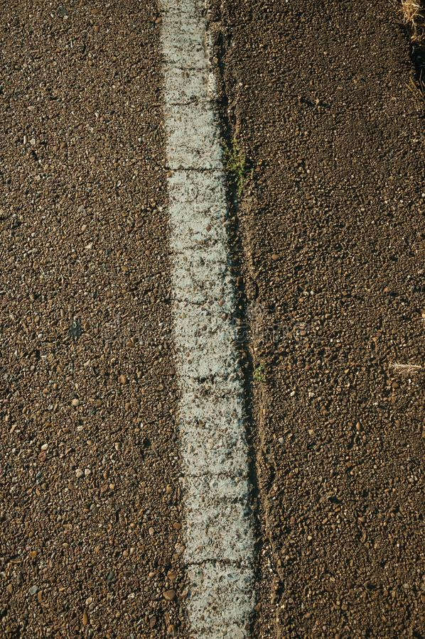 Close-up of asphalt and street lane on a road. Close-up of asphalt with small gravel inserted and a street lane, on a countryside road at sunset near Elvas. A royalty free stock photo