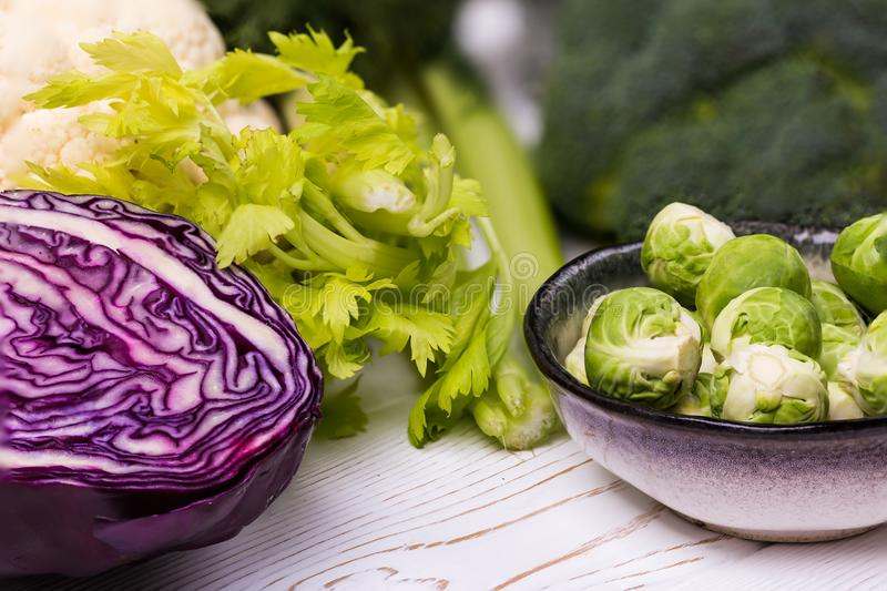 Close-up of assorted fresh vegetables on a white wooden table: cabbage, broccoli, cauliflower and Brussels sprouts and royalty free stock image
