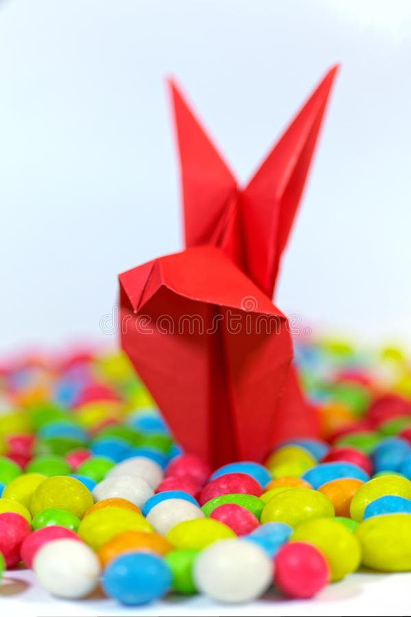 Close up of an assorted jelly beans and origami rabbits from paper. Easter bunny. Colorful sweet candy background. Shallow depth o royalty free stock photo