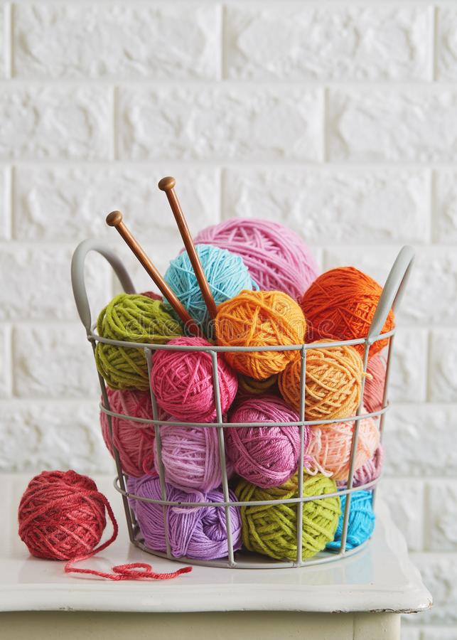 Knitting yarn balls and needles in basket. Close up of assorted yarn and wooden needles stock photography