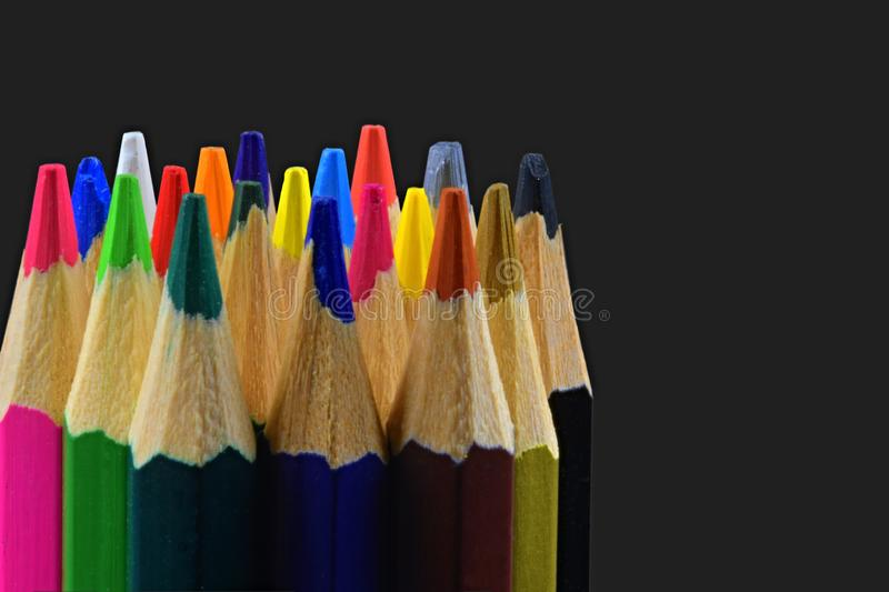Close up of an assortment of colored pencils tips on black background. Background of colorful pencils. Creative idea and stock photos