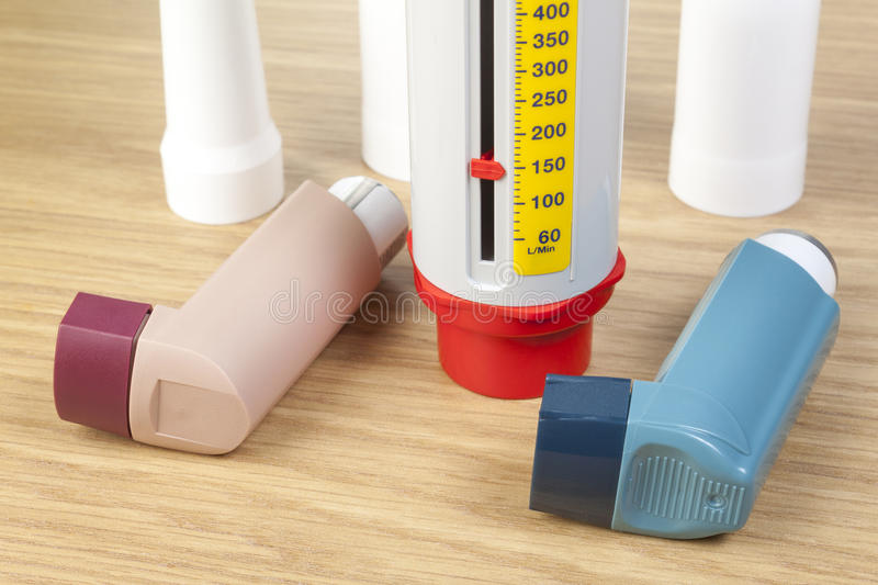 Close up of asthma inhalers and peek flow meter on table. Close up shot of a blue and a brown asthma inhaler laying on a table with a peek flow meter stock photo