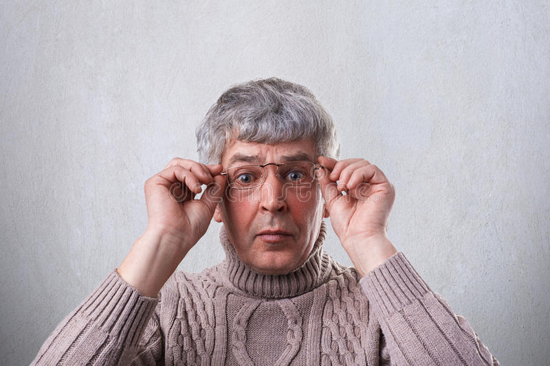 A close-up of astonished senior man wearing glasses and sweater holding his hands on the frames of glasses looking with wide opene stock images