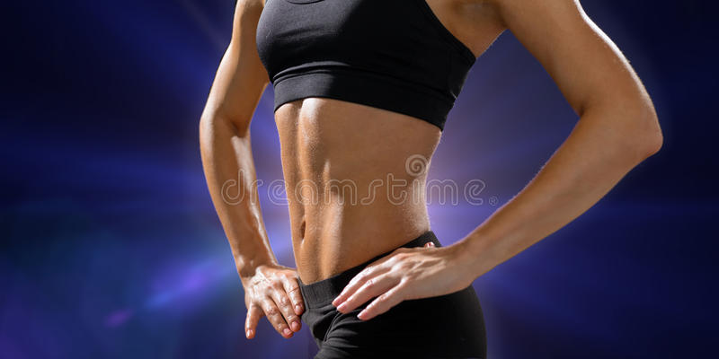 Close up of athletic female abs in sportswear. Fitness and diet concept - close up of beautiful athletic female abs in sportswear stock image