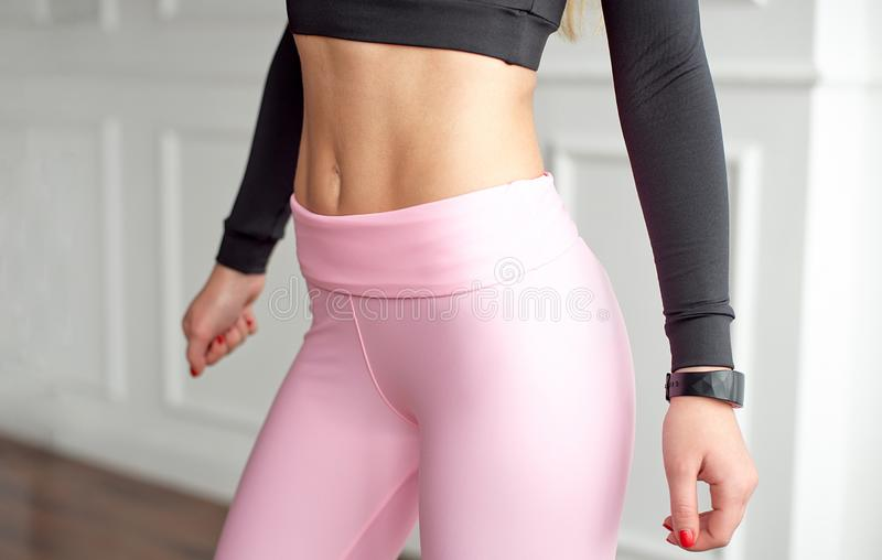 Close-up athletic female body slim elegant waist of a stylish fitness model with perfect figure lines after an effective. Training class, pumped up arms with a royalty free stock photography