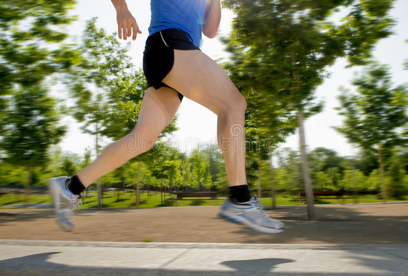 Close up athletic legs of young man running in city park on summer training in healthy lifestyle concept royalty free stock image