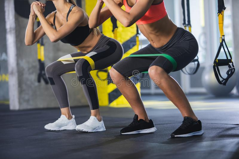 Two female are sitting-up with latex band indoors. Close up of athletic women in squat together in gym. Couple of fit girls are exercising with resistance band stock image