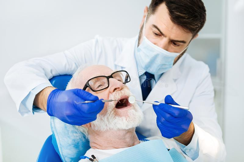 Close up of attentive stomatologist in the dental office. Loyal client. Close up of skilled stomatologist using dental equipment while the patient sitting on the royalty free stock images
