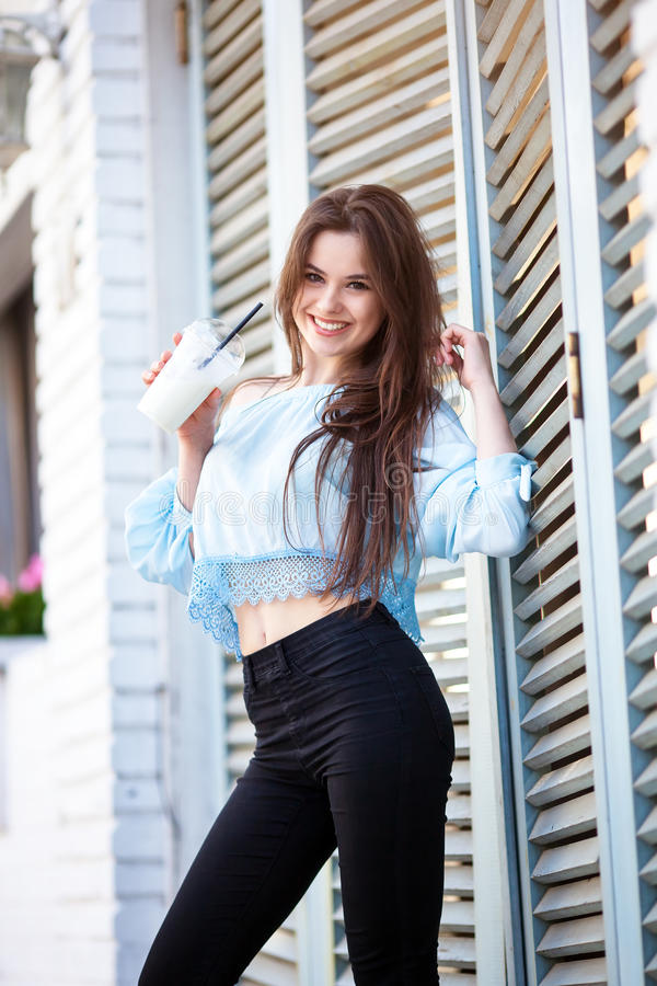 Close-up of attractive brunette girl with long hair standing near cafe. She wears Blue blouse with open shoulders royalty free stock images