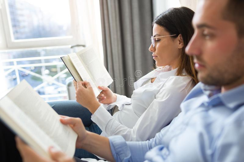 Attractive concentrated couple reading together while relaxing in bed at hotel room royalty free stock images