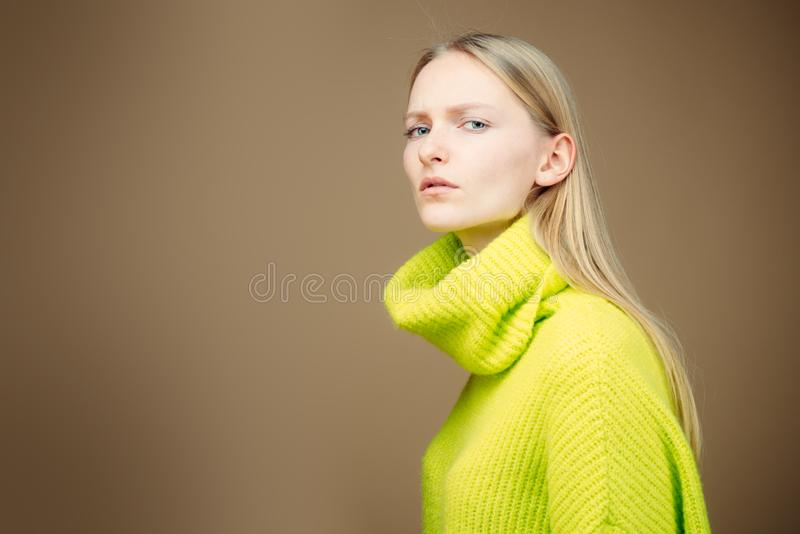 Close-up attractive european blonde woman long hair, tilting head, standing in a half-turn, wearing casual green outfit royalty free stock photo