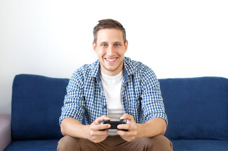 Close-up of an attractive guy with stubble in a shirt, holding a joystick and playing video games on TV on vacation, sits at home. On a cozy sofa, successful stock photos