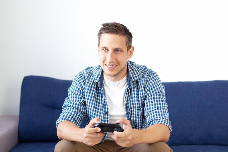 Close-up of an attractive guy with stubble in a shirt, holding a joystick and playing video games on TV on vacation, sits at home. On a cozy sofa, successful royalty free stock images