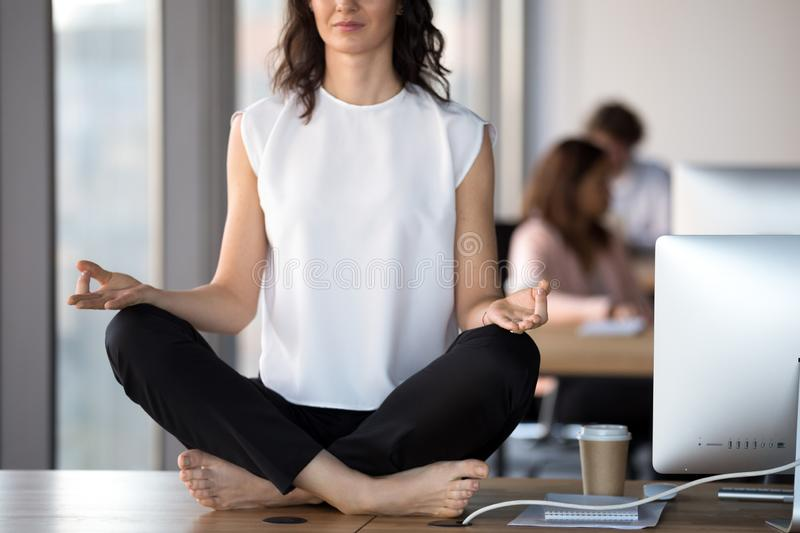 Barefoot businesswoman meditating sitting in lotus position on o royalty free stock photos