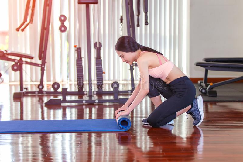 Close-up of attractive young asian woman folding blue yoga or fitness mat after working out at yoga class in sport club stock photos