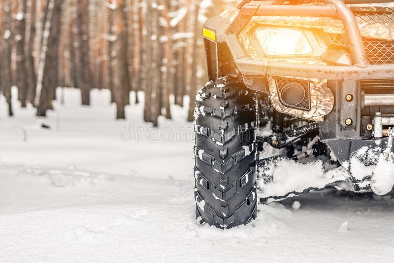 Close-up ATV 4wd quad bike in forest at winter. 4wd all-terreain vehicle stand in heavy snow with deep wheel track. Seasonal extre royalty free stock image